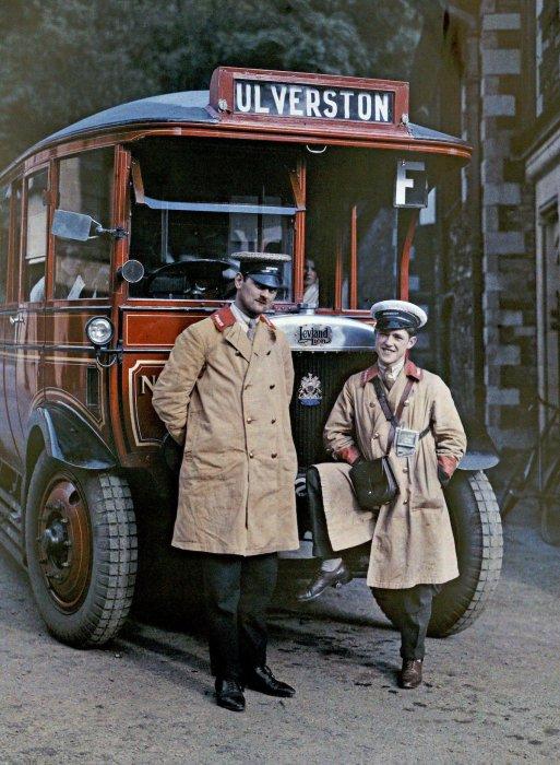Два водителя стоят перед туристическим автобусом в Улверстоне, Камбрия.