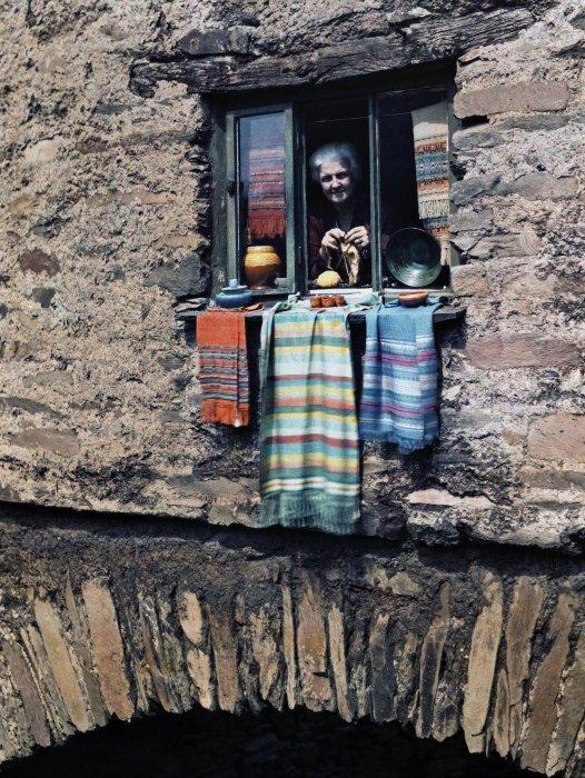 Женщина выглядывает из окна каменного дома в Эмблсайд, Лейк-Дистрикт (Озёрный край), Камбрия, Англия.