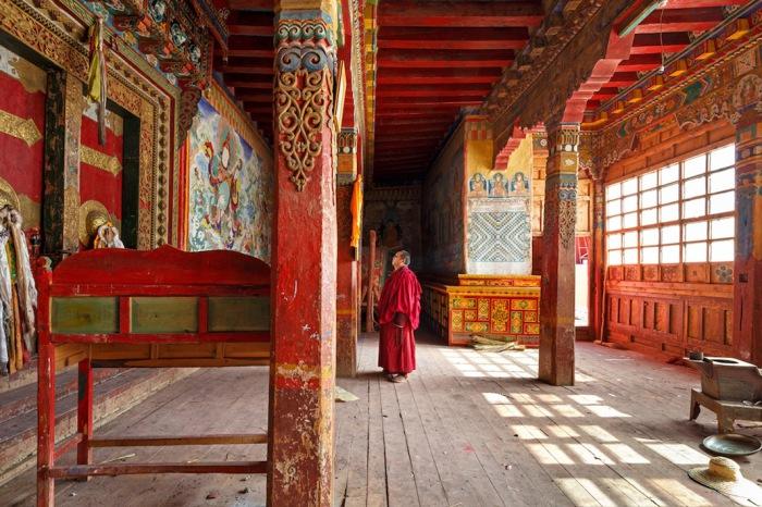 Монах у входа в монастырь Golo Gompa, Сычуань, Китай. Автор фото: Colin Miller.