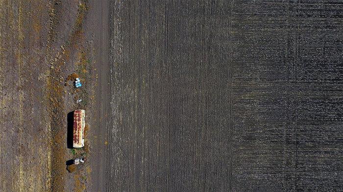 Старый автобус, используемый для хранения сельскохозяйственной техники, стоит в засушливом загоне на территории, расположенной к западу от города Ганнедах в Новом Южном Уэльсе, Австралия. Автор: David Gray.