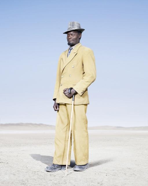 Мужчина-гереро в желтом костюме, фото 2012 год. Автор фото: Джим Наугтен (Jim Naughten).