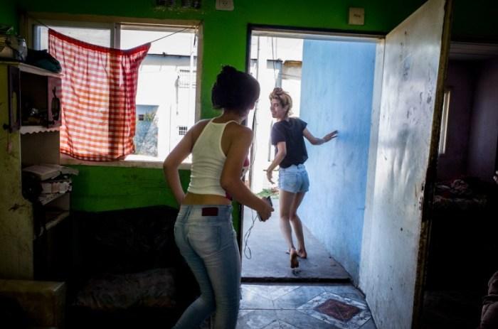 К. и одна из её младших сестер выбегают из своего дома. Автор: Karl Mancini.