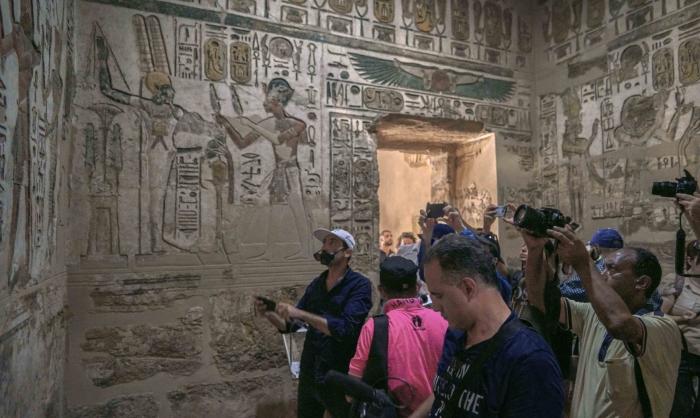 Журналисты и туристы фотографируют фрески внутри храма Хонсу в Карнаке.
