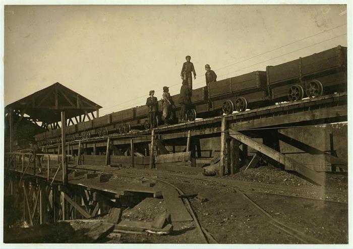 Мальчишки работают на движущихся платформах, которые перевозят уголь. Автор фото: Льюис Хайн (Lewis Hine).