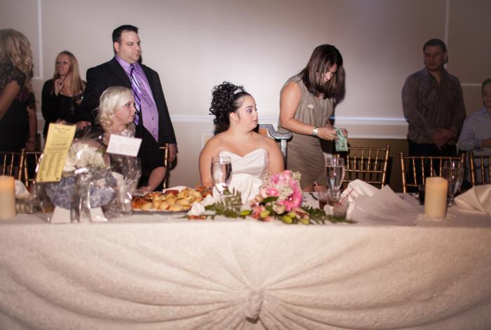 Риччина сидит во главе праздничного стола в окружении своих родных и близких.