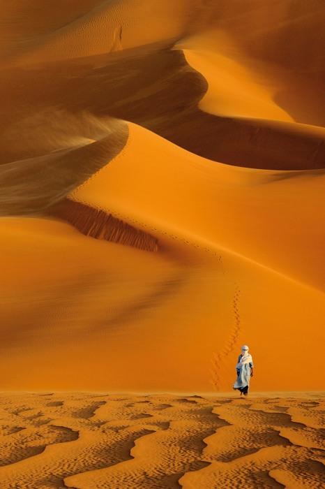 Мужчина, идущий по пустыне во время сильного ветра, в Туареги в Ливии. Автор: Marsel van Oosten.