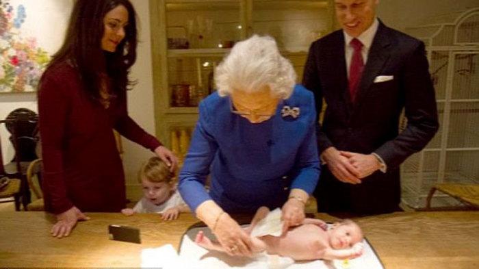 Королева Елизавета II пеленает малышку.