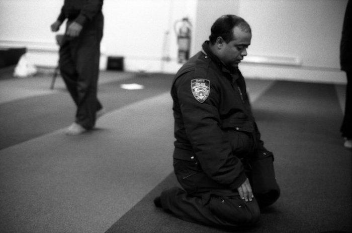 Офицер полиции  во время молитвы. Парк 51,  Манхэттен, Нью-Йорк, 2012 год. Автор: Robert Gerhardt.