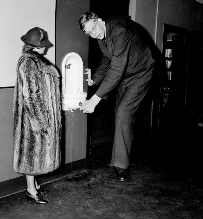 Уодлоу наклоняется, чтобы выпить воды в офисе Daily News в Нью-Йорке, 1937 год.