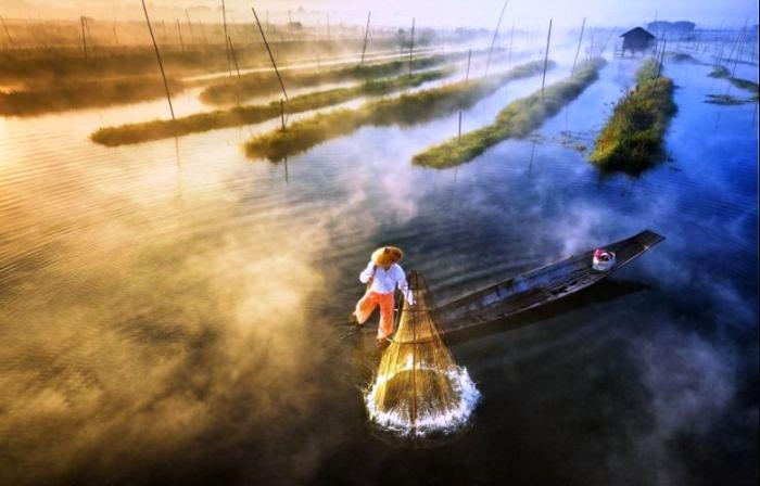 Рыбак Инта устанавливает свою сеть, чтобы ловить рыбу в озере Инле в Майанмаре. Автор: Zay Yar Lin.