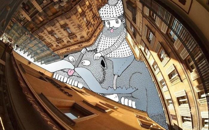 Перевёрнутая сторона: бородатый мужчина катается на кошке между зданиями. Автор: Thomas Lamadieu.