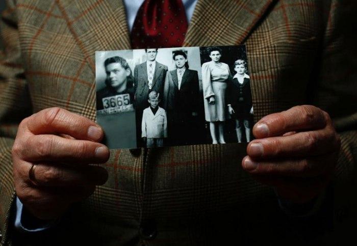 Яцек держит фотографию своей семьи. Все они были отправлены в лагерь.
