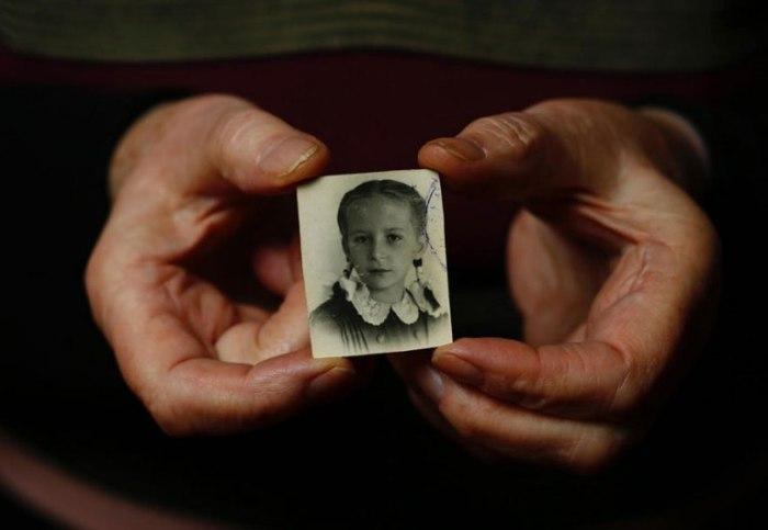 Барбара держит свою фотографию времен войны.