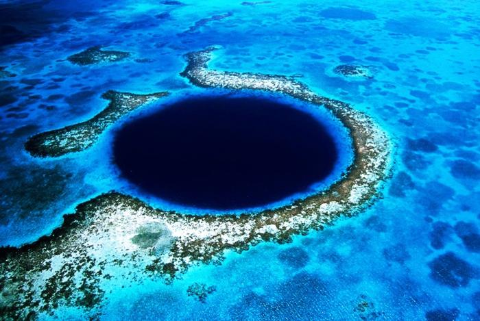 Большая голубая дыра, чернеет круглым провалом среди бирюзовых вод вблизи Белиза. Автор фото: Eric Pheterson.