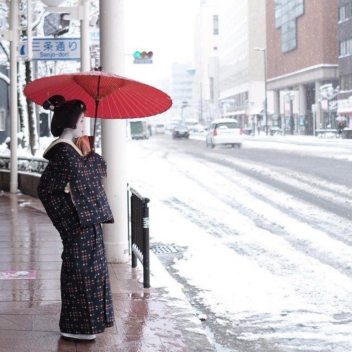 Гейша под красным зонтиком смотрит на снег.