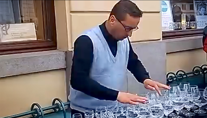 Уличный музыкант играет классику на бокалах.