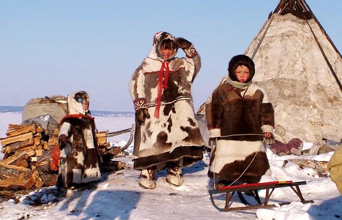 Манси в традиционных одеждах рядом с традиционным жилищем - чумом