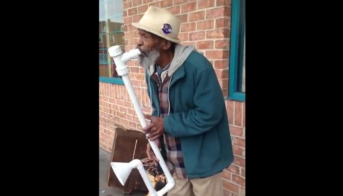 Уличный музыкант играет на самодельном саксофоне.