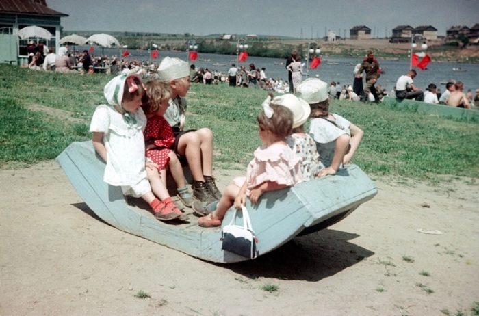 Девочки в нарядной одежде наблюдают за спортивными соревнованиями, которые проходят на озере.