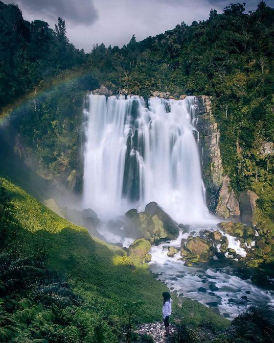 Падение воды с небольшой горы в лучах солнца и радуги.