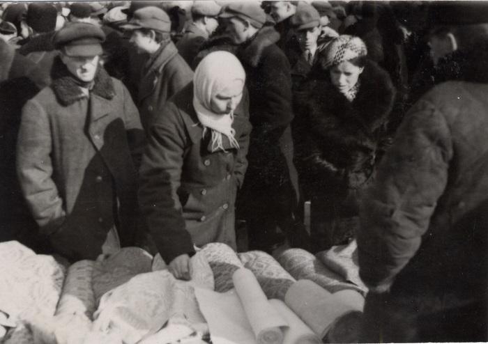 Женщина рассматривает ткань на сельском базаре, 1939 год.