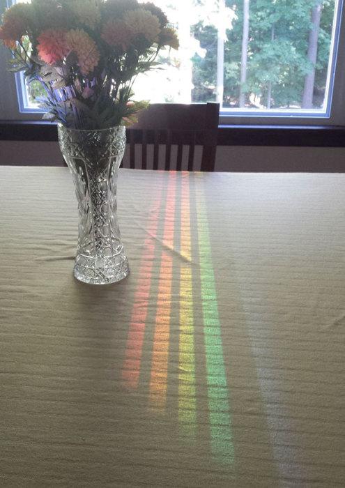 Сонячні промені потрапляють в кімнату через вікно, проходять через спинку стільця і відображаються у вазі.