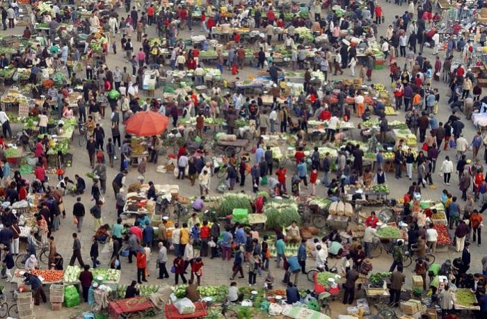 Люди покупают овощи на рынке в Пекине.