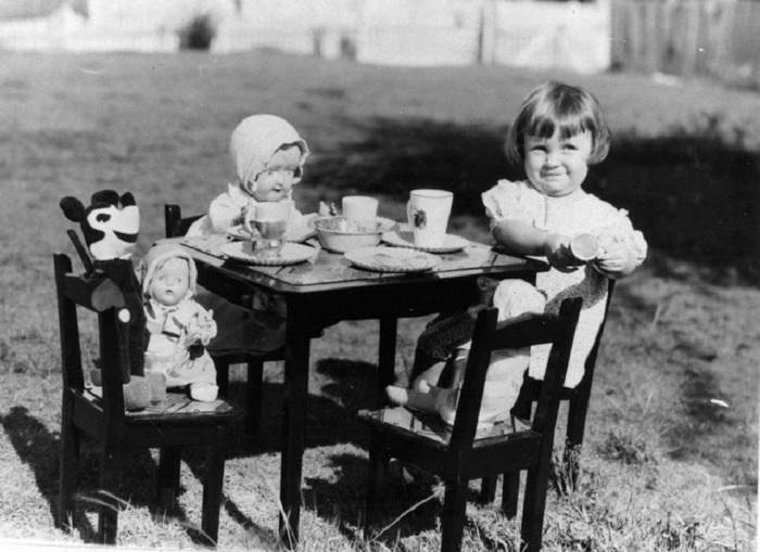 Маленькая девочка развлекает Микки Мауса и других игрушечных друзей и понарошку поет всех чаем, 1930-е годы.