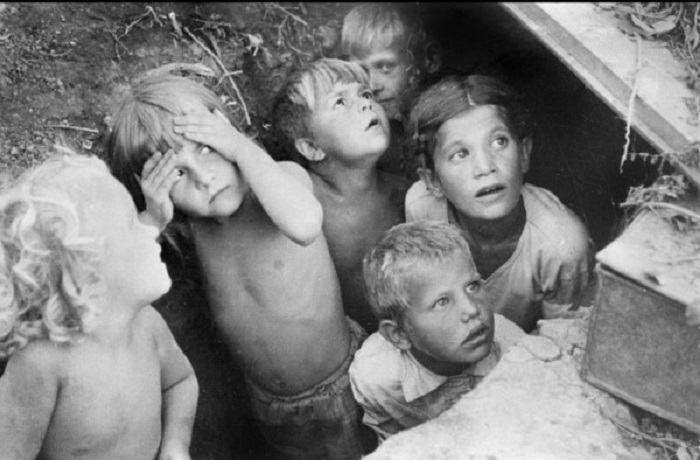 Дети прячутся от бомбёжки и смотрят с надежной в небо.