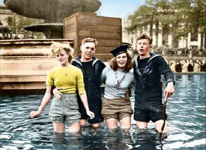 Британские матросы отмечают Победу с подругами в фонтане на Трафальгарской площади, Лондон, Великобритания.