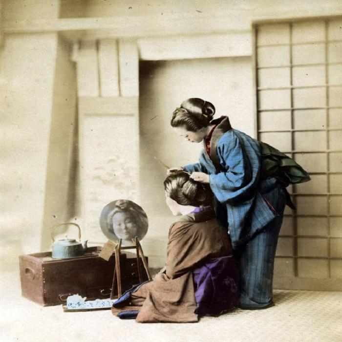 Мастерица аккуратно выкладывает волосы женщины в форме экзотического цветка.