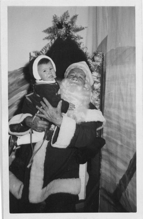 Санта в короткой куртке, с черным поясом и пряжкой, восседает с мальчиком на троне.