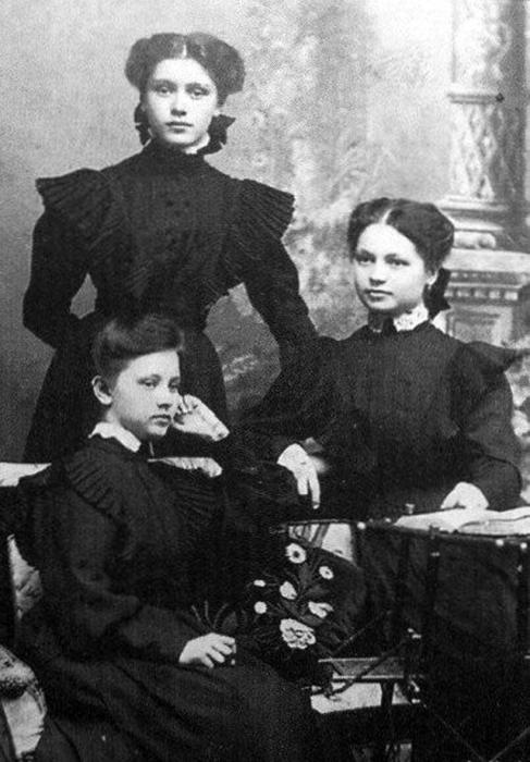 Ученицы класса одеты в темные платье с черным фартуком.