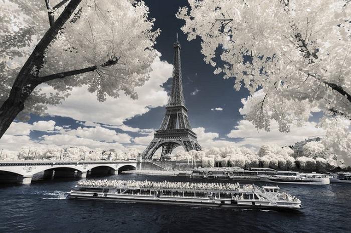 Грандиозное строение на берегу реки в белых облаках.