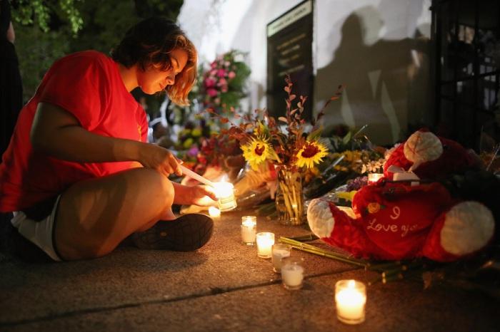 Женщина зажигает свечи в память о девяти жертвах стрельбы в Чарльстоне, Южная Каролина, США.