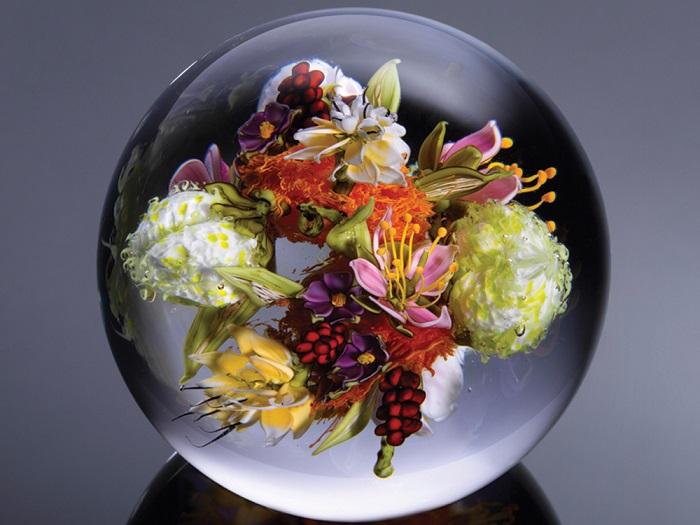 Композиция из разноцветных цветов отображена в стекле.