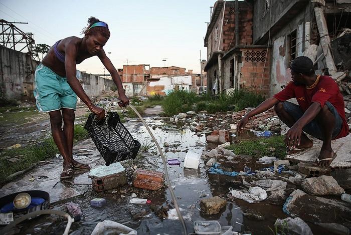 Люди моют посуду на улицах, просто поливая ее из лежащих на земле шлангов.