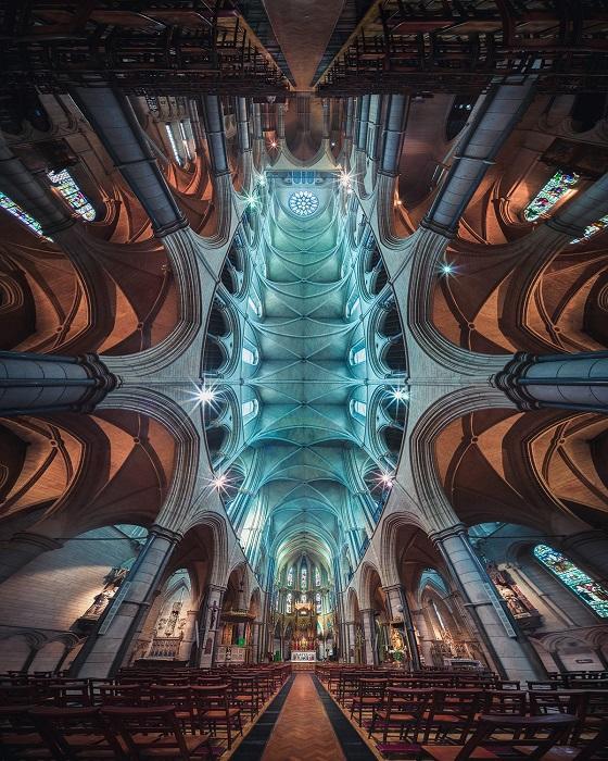 Сквозь высокие окна осеннее солнце освещает внутренне убранство готической римско-католической церкви Святого Джеймса в Лондоне.