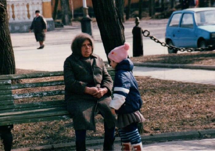 Бабушка присматривает за играющей внучкой с парковой скамейки.