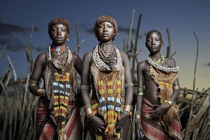Красивые, ухоженные люди в цветных повязках на бедрах, в металлических кольцах, браслетах и бусах, украшающие ноги, руки, шею.