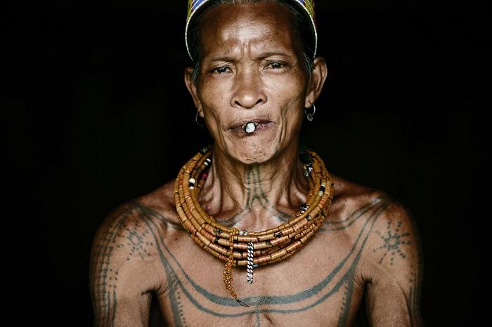 Воин народа ментавайцев в традиционном головном уборе и украшениях курит папиросу.