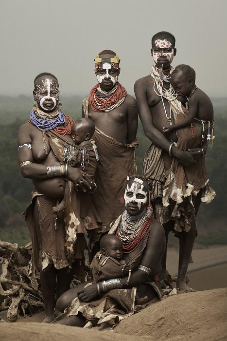 Представители племени каро с раскрашенными лицами, украшены яркими аксессуарами: бусами, украшениями из цветов и насекомых.