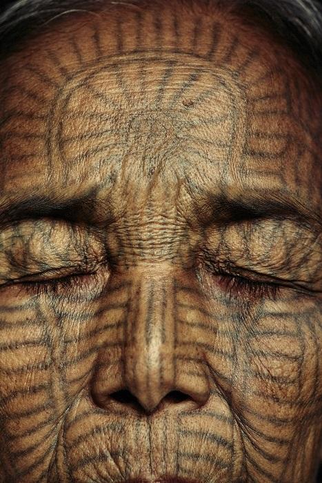Лицо пожилой женщины племени чин покрыто татуировками.