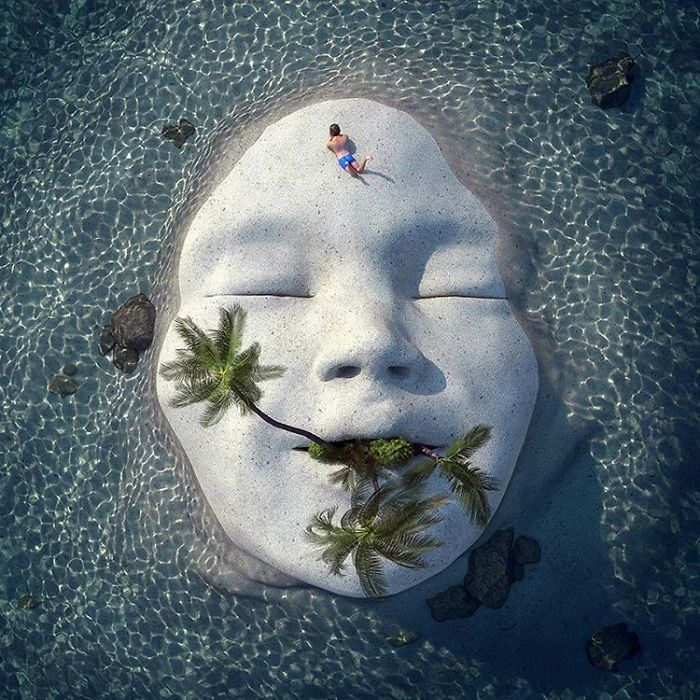 Мини остров в образе лица и растущих пальма, в окружении прозрачных вод.