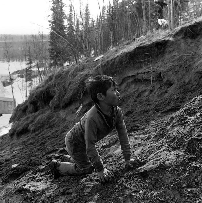 Мальчик играет с хаски стоя на четвереньках, Шунгнак, Аляска, 1973 год.