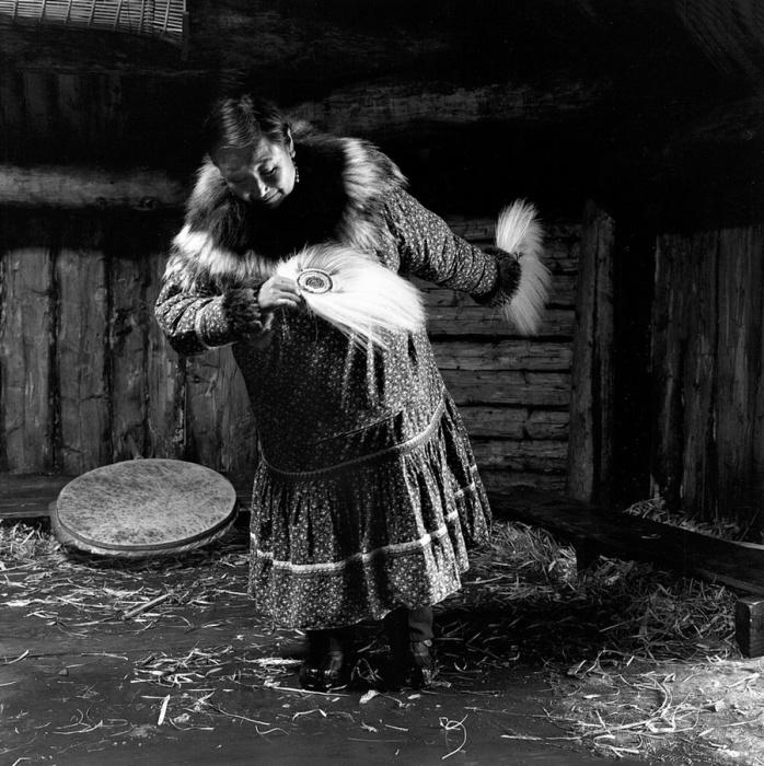 Пожилая женщина танцует танец с перьями и бубном. Тунунак, Аляска, апрель 1976 год.