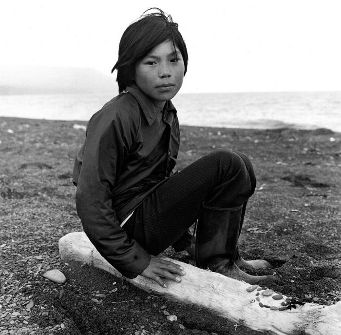 Ребенок в резиновых сапогах выкладывает из гальки узоры на бревне. Тунунак, Аляска, июль 1977 год.