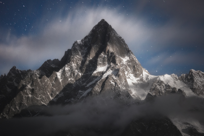 Ночной снимок, на котором запечатлена вершина пика Пуэнт-Уокер - освещенная мягким лунным светом и бережно прикрытая облаками.