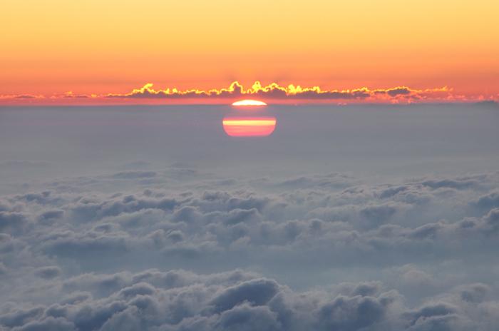 Вид на восходящее солнце, которое словно выплывает из облачного моря, с вершины горы Роччамелоне (3538 метров).
