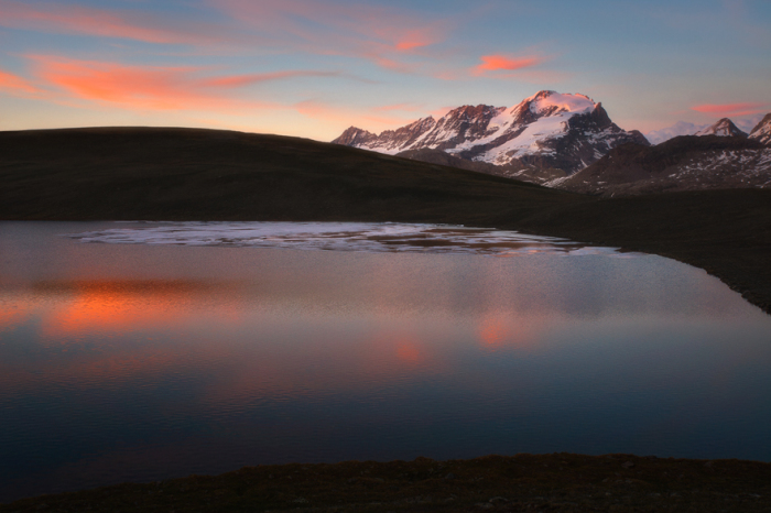 Спокойный и выразительный закат над озером Россет и горными вершинами в Национальном парке Гран Парадизо, Италия.